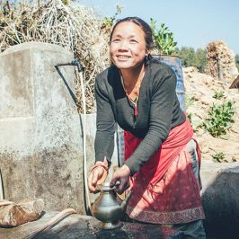 Woman using new water source in Nepal.