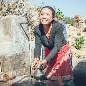 Woman uses fresh water source in Nepal   Ways to fight poverty