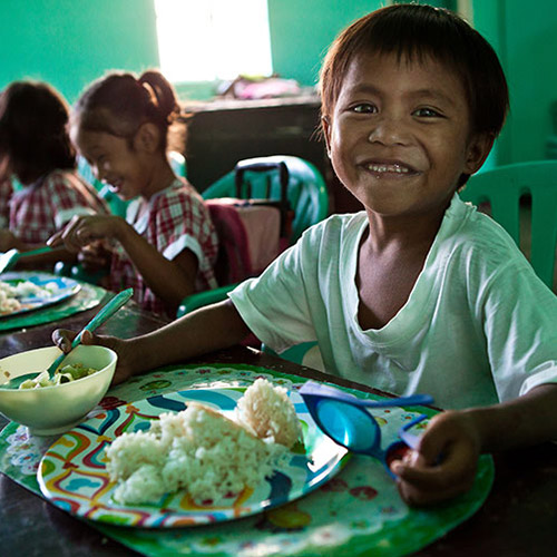 Child eating rice as part of Philippine feeding program