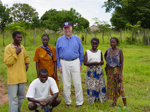 Bill Hidgon, one of the founders of Outreach International, poses with community members