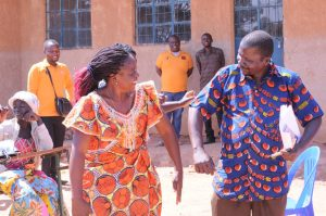 Literacy class instructor and student share a celebratory dance during graduation ceremonies