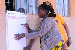 Literacy class graduate writes her name in front of the assembled crowd during graduation