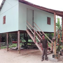 One of Outreach's Cambodian community partners poses in front of his home, refurbished with resources furnished by Habitat for Humanity Cambodia