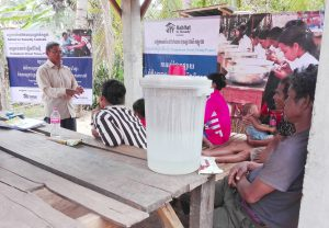 Facilitator Sopha [left, in white shirt] chats with Outreach-affiliated community members about the finer points of their new water filters, accessed through their partnership with Habitat for Humanity Cambodia.