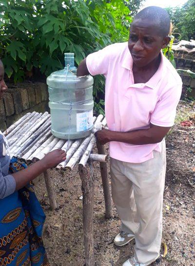 A community member from Zambia repairs a handwashing station