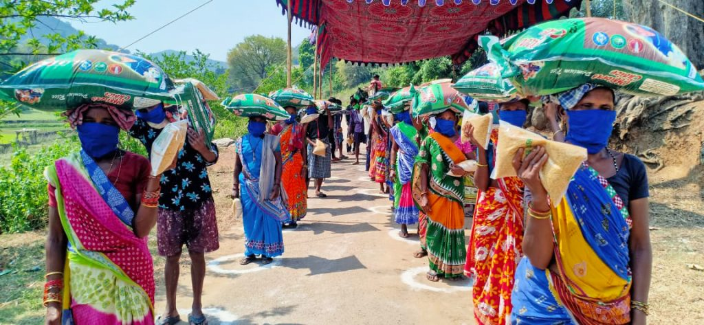 Community members in India observe social distancing measures while lining up to receive bags of rice and dal