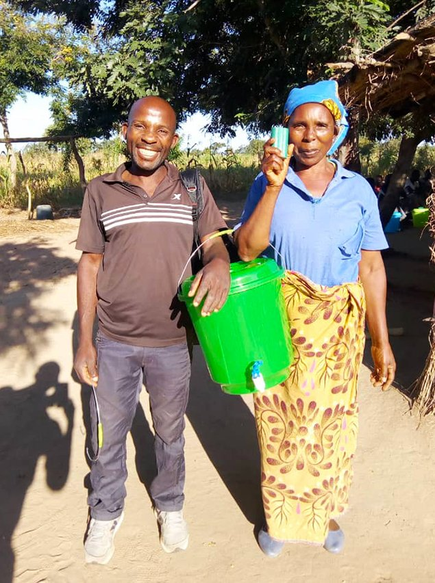 A husband-and-wife team of community leaders pose for a quick photo while distributing soap and buckets to homes.