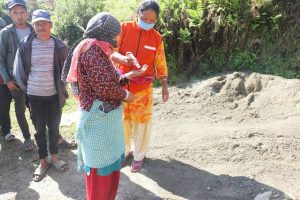 A community leader in Nepal shares hand sanitizer with a woman waiting in line for food supplies