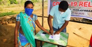 A community member from India gives a thumbprint to mark receipt of her food supply.