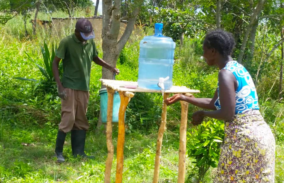 A woman demonstrates the new model of hand-washing station that now includes a wooden stand.