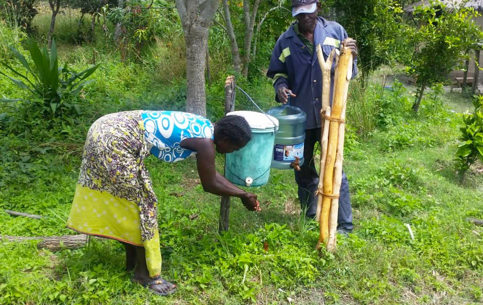 A woman demonstrates using the original model of a hand-washing station