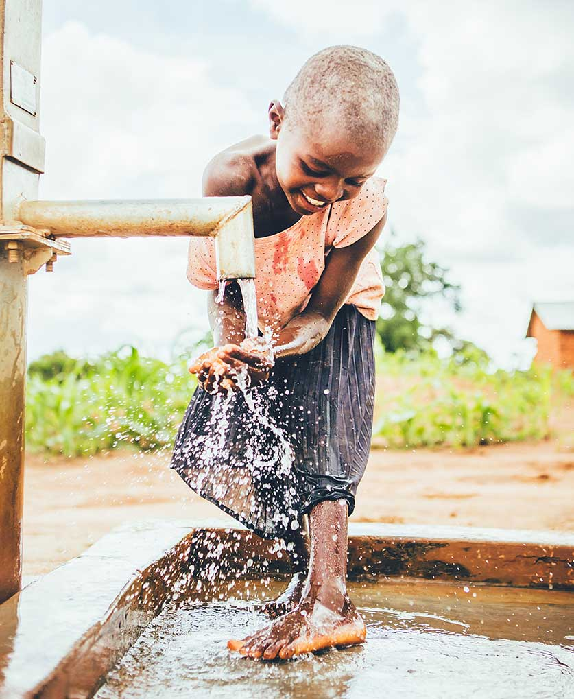 Child at water well in Malawi