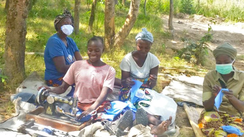 Clementina and her team share smiles and equipment as they work to produce face-masks for their community.