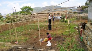 Community members in Nepal construct the outer portion of their veggie tunnels