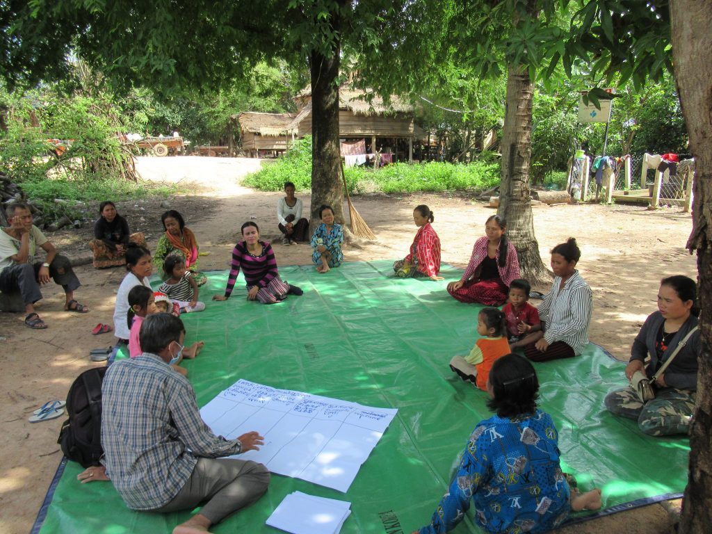 Community members in Leap Village, Cambodia meet with a member of Outreach Cambodia's field team