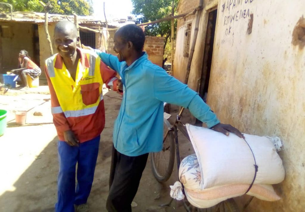 Two men from Congo share a laugh as they visit their community's food-loan program to receive some of the fruits (and vegetables) of their labor.