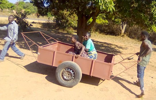 Kids enjoy a ride in one of their community's hand-carts, usually used for hauling supplies
