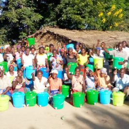 A community in Malawi poses with their newly acquired hand-washing basins.