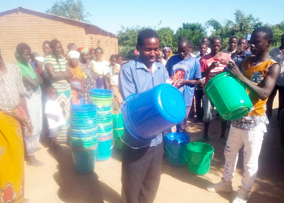 Community Members in Malawi receive their own buckets to use as hand-washing basins