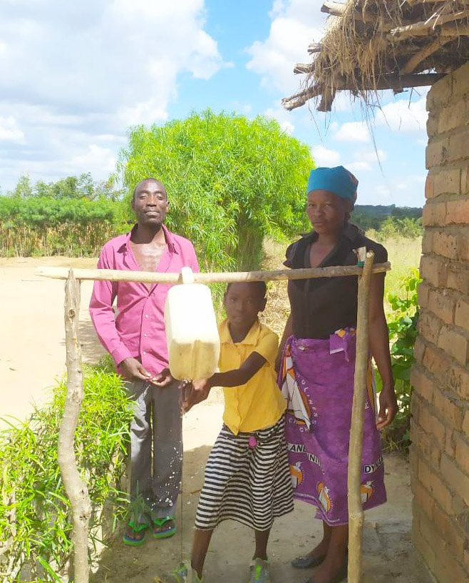 A family in Malawi shows off their touch-free hand-washing station