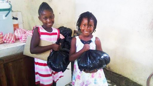 Girls from Outreach's Haiti Schools Feeding Program beam with gratitude after receiving their meal kits