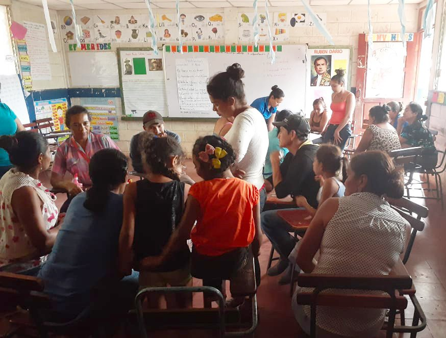 El Abra community members meet in a borrowed classroom to discuss, record and prioritize their issues