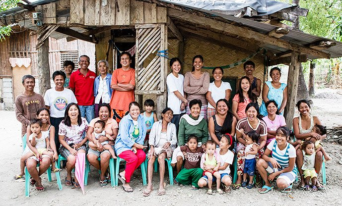 "A community in the Philippines poses for a group photo to celebrate their status as a ""graduate community"""