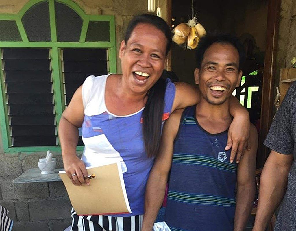 Renelyn with community member working on rice load project in Philippines