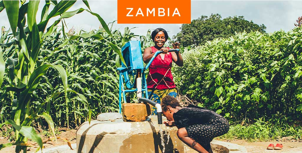 Woman and child at water pump in Zambia